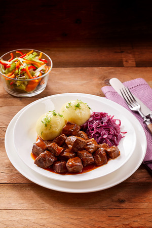 Tasty beef goulash in a rich gravy served with dumplings and shredded purple cabbage with a side dish of fresh salad , copy space above Stock Photo