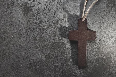 Basic cross on concrete background for grief card. Brown wooden crucifix on grey background with copy space .