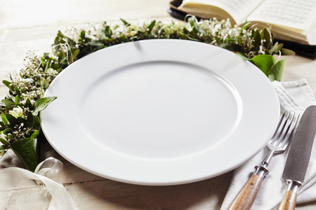 Empty white dish decorated with flower wreath and ribbon with fork and knife cutlery set on napkin and open book on wooden table