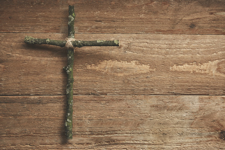 piety: Simple rustic homemade cross pf knotted green twigs on a rustic wood background with copy space for your religious or Easter themed text