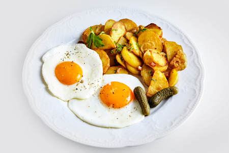 sunny side up: Two fried eggs seasoned with ground black pepper served with gherkin and crisp golden roast potato flavored with bacon pieces and rosemary, high angle view