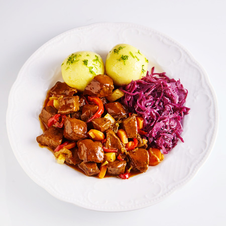 Spicy german beef platter with potato dumplings topped with herbs beside shredded cabbage