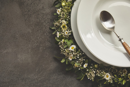 Vintage spoon inside empty white plate served on dark grey surface table with wreath of green leaves and daisy flowers. Copy space background