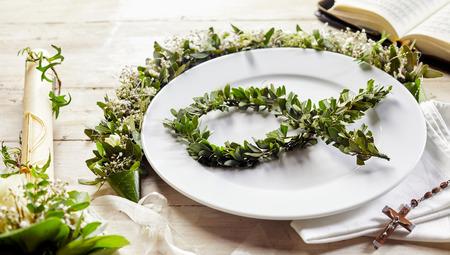 santa cena: Anglicana símbolo cristiano santa con la vela en una mesa con el plato y el arreglo floral decorativo. Foto de archivo