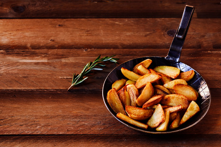 Crispy golden fried potato wedges with fresh rosemary seasoning served in an old metal skillet on a rustic wood background with copy space, high angle view