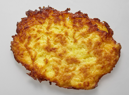 Single isolated rosti or reibeplatzchen on grey, traditional swiss and German grated potatoes pan fried to a crisp golden fritter