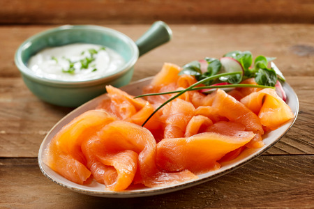 appetizers: Healthy slices of smoked salmon fillet topped with fresh herbs served on a plate with creamy cheese or sour cram sauce, close up view