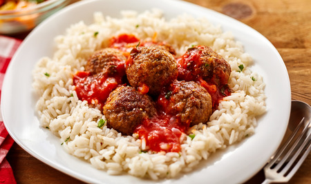 High Angle Still Life of Homemade Meatballs in Tomato Sauce on a Bed of Fluffy Seasoned Rice Served in Modern White Bowl on Wooden Table with Cutlery