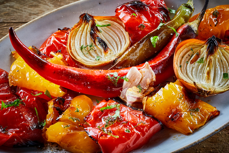 ovenbaked: Colorful healthy roasted or oven-baked vegetables with sweet pepper, chili or cayenne pepper, tomato, onion garnished with chopped fresh herbs, close up view