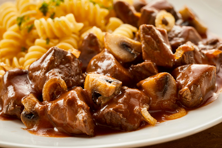 Elevated view of freshly made Hungarian goulash with garnished pasta on plate