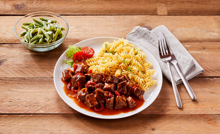 side of beef: Small bowl of green beans side dish on table with serving of spicy beef and plain corkscrew pasta