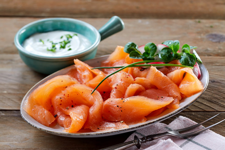 Gourmet platter of fresh smoked salmon rich in omega-3 fatty acids with herbs served with a creamy chive sauce on a rustic wooden table , low angle close up view