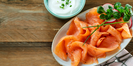 Fresh slices of healthy smoked salmon or lok served with a creamy chive sauce on an oval platter viewed from above on wood with copy space, panorama banner format