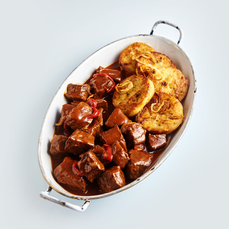 Tasty spicy beef goulash with sliced roasted dumplings and onion served in an old metal oval dish, high angle view on white