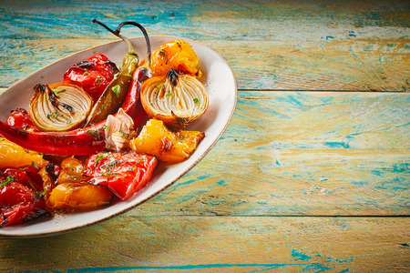 marinade: Healthy vegan and vegetarian cuisine with a colorful platter of fresh roasted vegetables with cayenne pepper, sweet pepper, garlic, onion and tomato seasoned with herbs on rustic wood with copy space