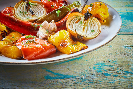 ovenbaked: Colorful platter of healthy roasted vegetables with sweet pepper, tomato, garlic, onion and whole chili or cayenne pepper to serve as an accompaniment or appetizer Stock Photo
