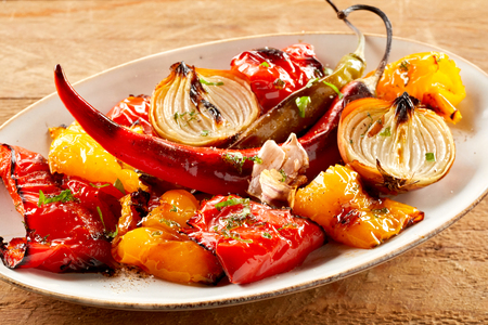Delicious healthy plate of roasted vegetables seasoned with fresh herbs with colorful bell pepper, tomato, chili pepper, garlic and onion for a vegetarian cuisine