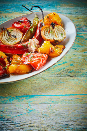 vegetarian cuisine: Fresh healthy organic roast vegetables for tasty vegetarian cuisine with sweet peppers, chili pepper, onion, tomato and garlic in a close up view on old rustic wood with copy space