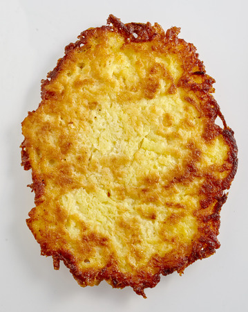 Pan-fried German or Swiss rosti potato fritter cooked to a crispy golden texture isolated on white in a concept of regional cuisine Imagens