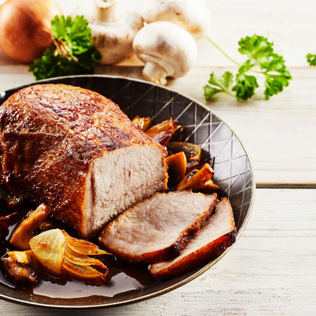 natural juices: Succulent tender veal roast with onion and mushrooms served in its natural juices in an old metal skillet, close up square format view with ingredients behind Stock Photo