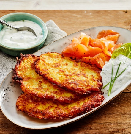 Close Up Still Life of Golden Crisp Potato Rosti Pancakes Served on Decorative White Plate with Smoked Salmon and Creamy Dill Sauce on Wooden Table with Napkin Stock Photo