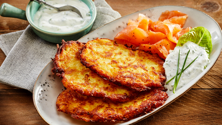 Close Up Still Life of Golden Crisp Potato Rosti Pancakes Served on Decorative White Plate with Smoked Salmon and Creamy Dill Sauce on Wooden Table with Napkin Zdjęcie Seryjne - 72205564
