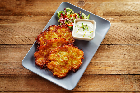 High Angle Close Up of Trio of Crisp Fried Potato Rosti Patties Served on Modern Rectangle Plate with Side Salad and Creamy Dressing Dip Served on Rustic Wooden Table with Copy Space