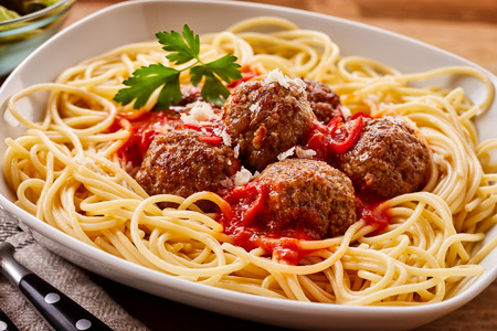 Close Up Still Life of Homemade Meatballs in Tomato Sauce on a Bed of Spaghetti Noodles Served in Modern White Bowl on Table with Cutlery