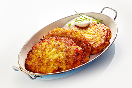 High Angle Still Life of Golden Crisp Fried Potato Rosti Pancakes Served in Dish with Creamy Dill Sauce on White Background Imagens