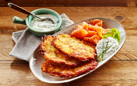 Close Up Still Life of Golden Crisp Potato Rosti Pancakes Served on Decorative White Plate with Smoked Salmon and Creamy Dill Sauce on Wooden Table with Napkin Фото со стока