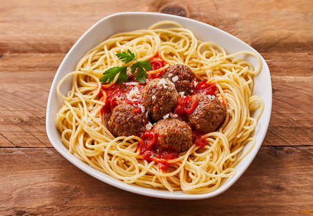 potherb: High Angle Still Life of Homemade Meatballs in Tomato Sauce on a Bed of Spaghetti Noodles Served in Modern White Bowl on Rustic Wooden Table Stock Photo