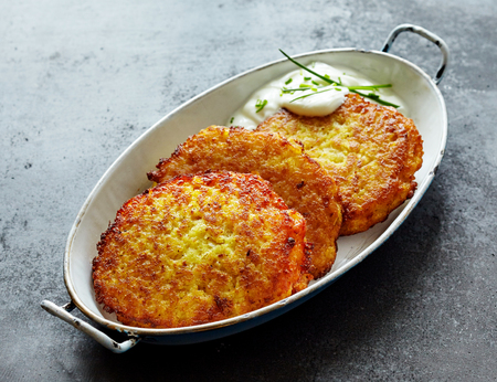High Angle Still Life of Golden Crisp Fried Potato Rosti Pancakes Served in Dish with Creamy Dill Sauce on Textured Gray Counter Surface