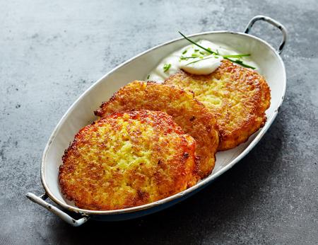 High Angle stilleven van Golden Crisp Fried Potato Rosti pannenkoeken geserveerd in schaal met romige dillesaus op getextureerde grijze aanrecht