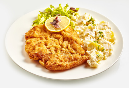 Fried Wiener schnitzel with side dish, lemon and lettuce on white plate close-up over white background Reklamní fotografie