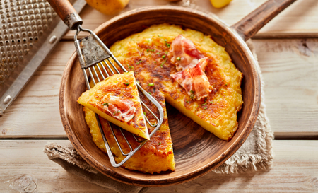Tasty crispy golden pan-fried Austrian potato fritter served in the pan with a single portion displayed on a spatula above in a rustic kitchen with utensils, overhead view
