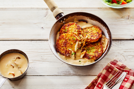 High Angle Close Up of Golden Crisp Fried Potato Pancakes in Pan with Creamy Sauce and Sliced Apples Served on Wooden Table with Copy Space, Napkin and Cutlery