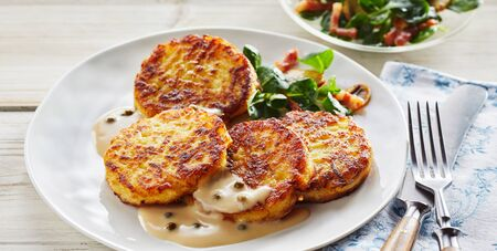 Close Up of Crisp Fried Potato Pancakes in Creamy Sauce with Capers Served on Modern White Plate with Side Salad Served on Table with Napkin and Cutlery Foto de archivo