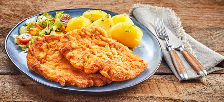 Schnitzel pieces with boiled potatoes and salad served on grey plate with cutlery on rustic wooden table surface
