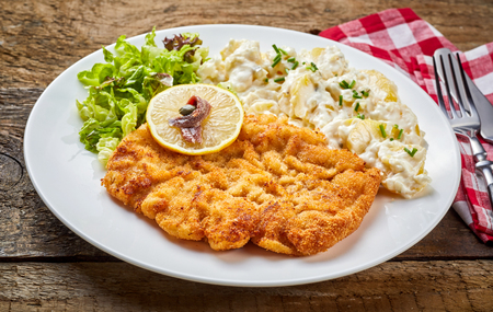 Schnitzel served with salad, lemon and side dish on white plate with cutlery on rustic rough wooden table Stock Photo