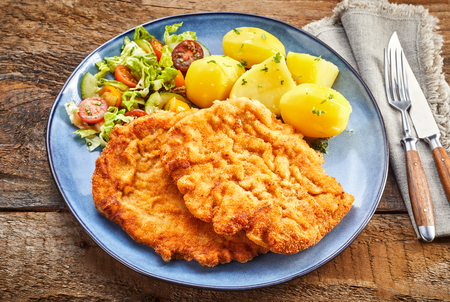 Served schnitzel with boiled potatoes and salad on blue dish shot from above with cutlery over grey napkin on rustic wooden table surface