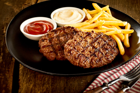 stakes: Minced meat barbecued stakes served with french-fries and bowls of sauces on black dish on rustic old wooden table Stock Photo
