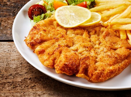 Schnitzel served with French fries, lemon and vegetable salad close-up on white dish over rough wooden surface background
