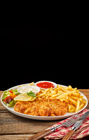 Schnitzel with French fries, vegetables and sauces set, served on white dish with cutlery over red napkin on wooden table. Menu or recipe concept with black background copy space
