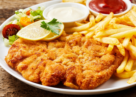 Schnitzel and French fries dish served with ketchup and mayonnaise, lemon and vegetables, close-up on white plate