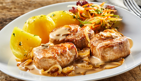 White dish with pork fillet pieces and boiled potatoes served with gravy, onion and vegetables on white plate on wooden table Stock Photo