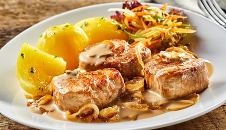 Witte schotel met stukjes varkensfilet en gekookte aardappelen geserveerd met jus, ui en groenten op witte plaat op houten tafel