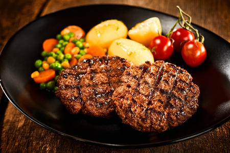 Minced meat steaks with potato and vegetables served on black dish with cherry tomatoes