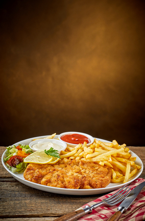 Schnitzel and French fries, vegetables and bowls with sauce on white dish, served with cutlery over red napkin on wooden table. Menu or recipe concept with blank background copy space