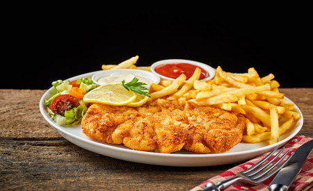 Dish of Wiener schnitzel and French fries served with sauces and salad on rustic wooden table against black background