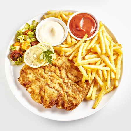 From above dish of schnitzel served with French fries, vegetable salad, lemon and ketchup with mayonnaise over white background